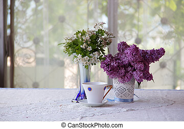 Still-life with tea and a lilac bouquet