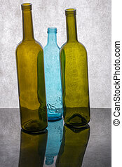 Still life with three colored glass bottles on a gray background