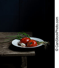 Still life with tomatoes and scallions on old wooden table.