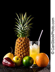 Still life with tropical fruits and glass of juice on a black reflective background with drops of water