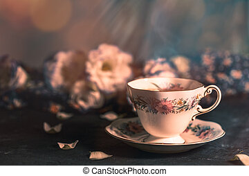 Still life with vintage cup of tea and flowers
