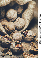 Still life with walnuts and cracked shells in vintage burlap bag.