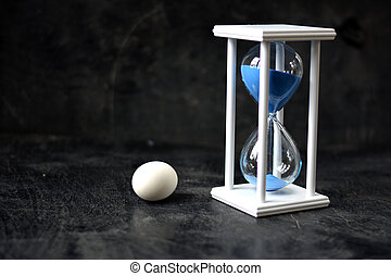 Still-life with white egg and sandglass on black background