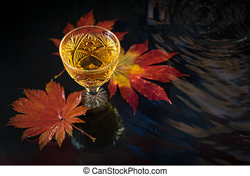 still life with wine in a crystal glass on the background of red maple leaves.