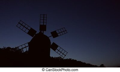 Still motionless windmill silhouette. Blue sky background.