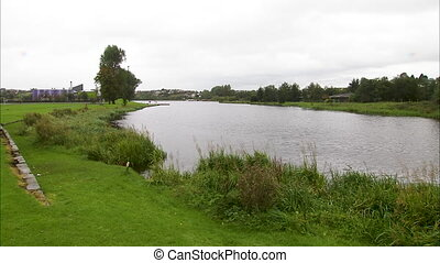 Still shot of a green Irish river surrounded by grass, trees and houses.
