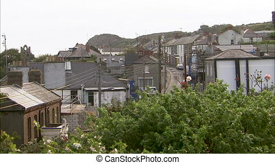 Still shot of a small Irish town surrounded by green and rocky hills and trees.