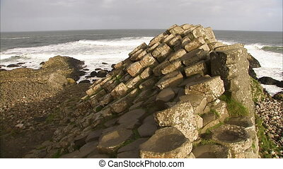 Still shot of an interesting rock formation along the rocky Irish shoreline. Waves crash into the rocks in the background.
