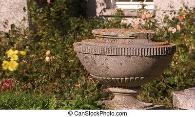 Still shot of an old decaying concrete flower pot, shot in an overgrown garden of an old house.