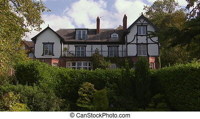 Still shot of an old three story house, with its large green...