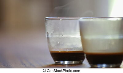 A still shot of steam flowing from two lattes that are on the table.