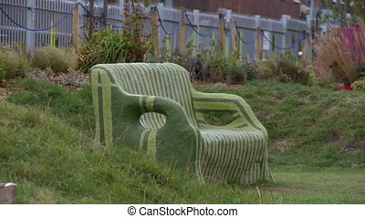 Still shot outdoors of striped bench, constructed from clay and surrounded by flora and plants
