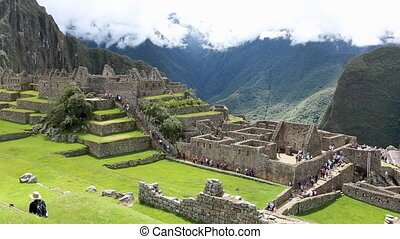 Still shot overlooking tourists walking around the abandoned and ancient incan structures on Machu Picchu