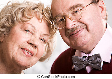 Still together - Two smart elderly people looking at camera ...