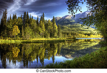 Still waters flowing into the Kenai River in Alaska in fall with tree reflections in the water.