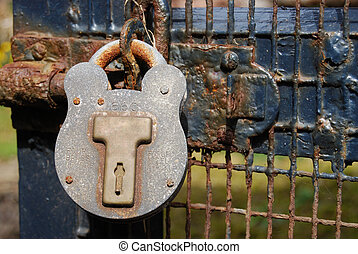 Still working? - old rusty lock on a wooden gate