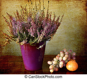 stilll life: heather pot and autumnal fruits on a wooden table