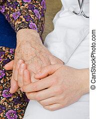 Stillness - The doctor holding an elderly woman's hand.