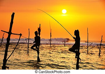 Silhouettes of the traditional fishermen at the sunset in Sri Lanka.