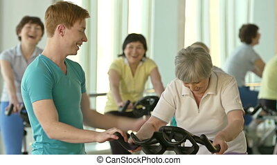 Stimulations - Young instructor motivating senior woman to...