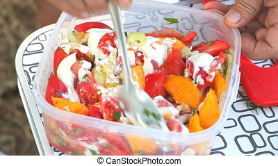 Stir a salad of tomatoes with a spoon