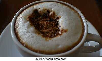 Stir and brew red sugar in to hot coffee in white cup on...