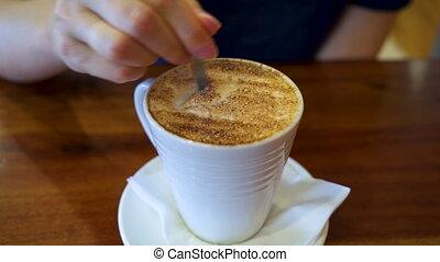 Stir capuccino in a white mug - Stir capuccino foam in a...