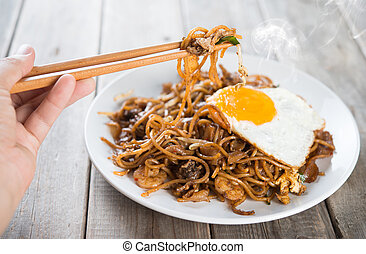 Stir fried Char Kway Teow - Close-up human hand holding...