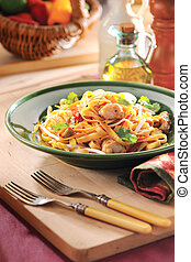 Stir fried pasta with mushroom on wooden board