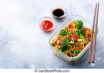 Stir fry noodles, udon with vegetables in glass lunch box. Grey stone background. Copy space.