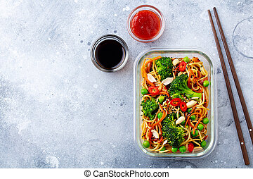 Stir fry noodles, udon with vegetables in glass lunch box. Grey stone background. Top view. Copy space.