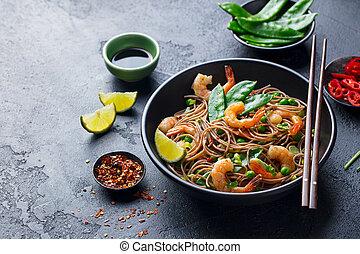 Stir fry noodles with vegetables and shrimps in black bowl. Slate background. Close up. Copy space.