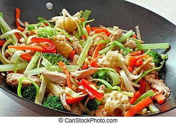 Mixed stir fry vegetables with chicken in a wok close up