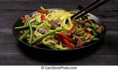Stir fryed noodls with garlic sprouts and chopped pieces of ...