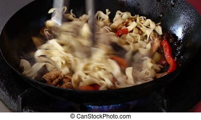 Stir frying noodles and vegetables in wok pan - Close up...