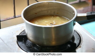 stirred ladle chicken soup in saucepan on gas stove