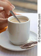 stirring coffee - woman\\\'s hand stirs coffe