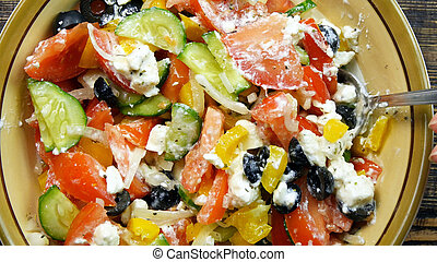Stirring fresh vegetable salad with cheese feta in the kitchen . The mixing of vegetables. Close-up