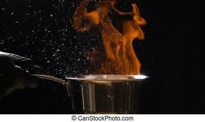 Stirring pan with burning sauce and hot droplets on black...