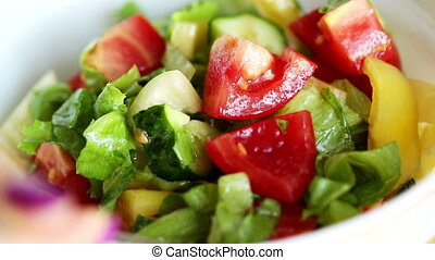 Stirring salad vegetables: tomatoes, cabbage, cucumbers,...
