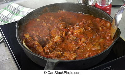Stirring spaghetti sauce with meat in a cast iron skillet