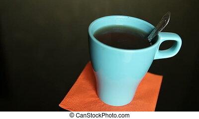 stirring tea in a blue cup