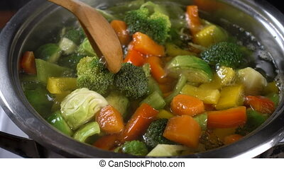stirring vegetable soup with a wooden spoon