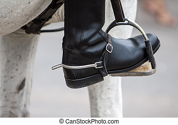 close up of a black leather boot on stirrup