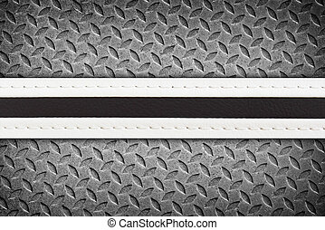 stitched leather on steel plate background.