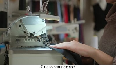 Stitching on sewing machine. Tailor sews on sewing machine. Close-up of woman's hand and sewing process. Small business fashion concept
