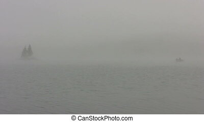 small boat on foggy lake