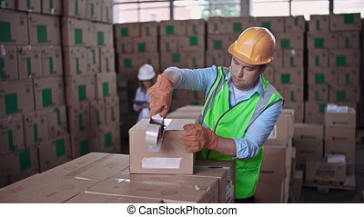 Stock Control - Close up of worker packing merchandise while...