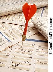 close up of stock market graphs and dart bulls eye