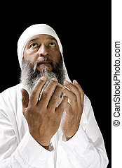 Stock image of Arab man praying over black background, selective focus on hands
